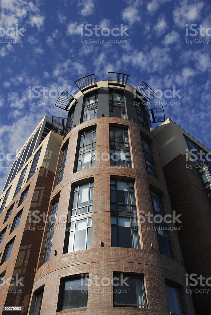 Building with sun visor and cotton-ball clouds stock photo
