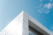 Building with white aluminum facade and aluminum panels against blue sky.
