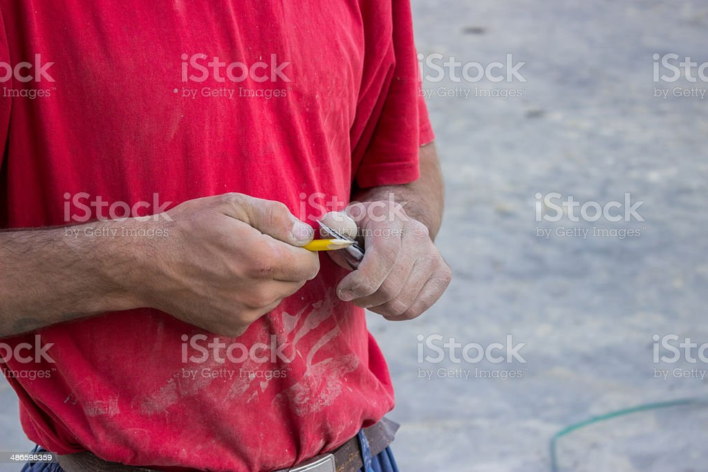 Building worker sharpening a pencil with a knife stock photo