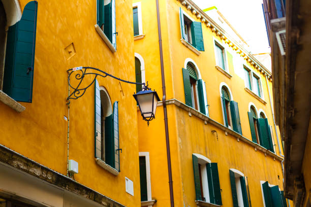 Building yellow wall with green windows Behind Lamp post on street view, idea for your background stock photo