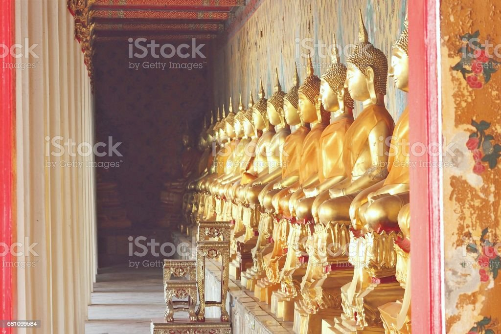 Buildings and Gold Buddha statues and clothed in yellow robe stock photo