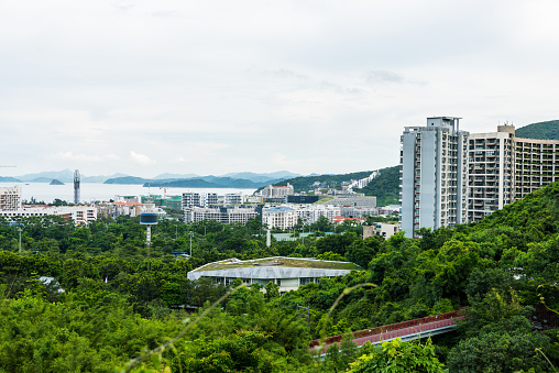 Buildings and sea at the costline of Shenzhen, view from the valley at Shenzhen Overseas Chinese Town East (OCT East) in Guangdong, China