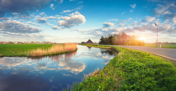 Buildings and trees near the water canal at sunrise in Netherlands. Colorful blue sky with clouds. Summer landscape. Rural scene. Cloudy sky reflected in water. Nature background. Vintage style stock photo