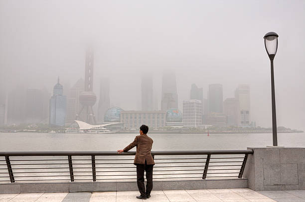 Buildings at Lujiazui are shrouded in heavy smog, Shanghai, China. Shanghai, China - April 20, 2010: Air Pollution, high-rises shrouded in heavy smog,  air in City remained severely polluted, man standing on the Bund, and looks at the Pudong District. huangpu river stock pictures, royalty-free photos & images
