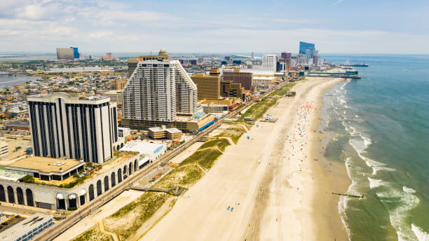 Buildings Boardwalk and Skyline of Atlantic City New Jersey The boardwalk at Atlanic City can be seen here extending all up the ocean coast boardwalk stock pictures, royalty-free photos & images