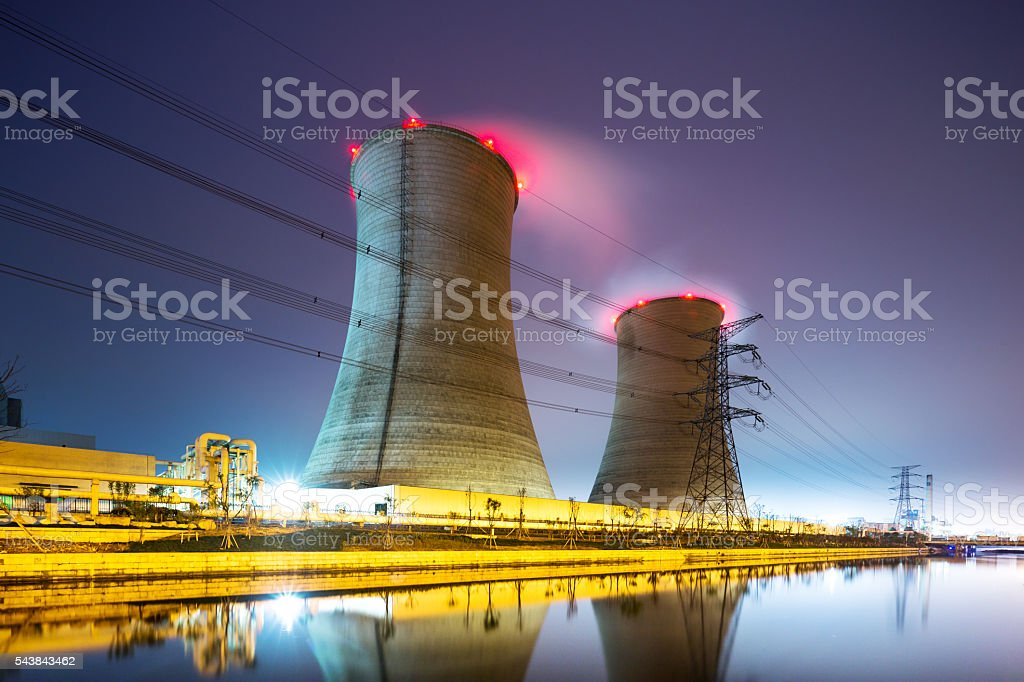 buildings of modern power station near river at twilight stock photo