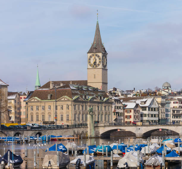 Buildings of the historic part of the city of Zurich along the Limmat river in winter, tower of the St. Peter Church above them stock photo