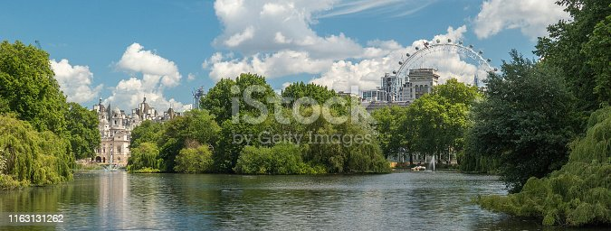 Buildings of the House Guards and the London Eye, as seen from St. James Park, London, United Kingdom. Pond in the foreground