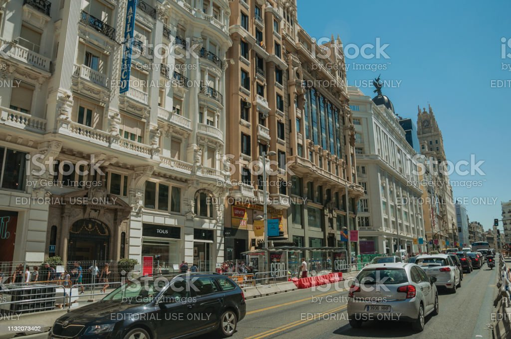 Madrid, Spain - July 25, 2018. Old buildings with shops on busy...