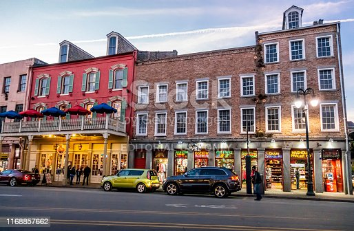 New Orleans, USA - Dec 11, 2017: Buildings with unique retro-styling architecture along Decatur Street. View at dusk with street lights, parked cars and people on road.