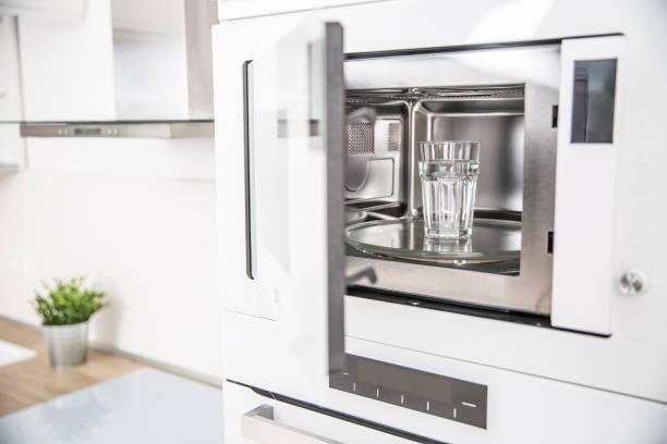Eingebaute Mikrowelle in der Küche mit einer Tasse reinem Wasser – Foto