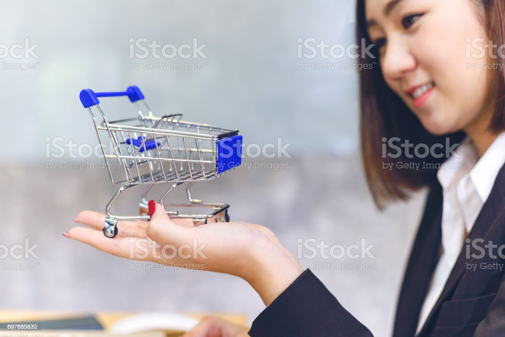 Buisiness woman holding shopping cart in online shopping concept. Business Workplace strategy Concept stock photo