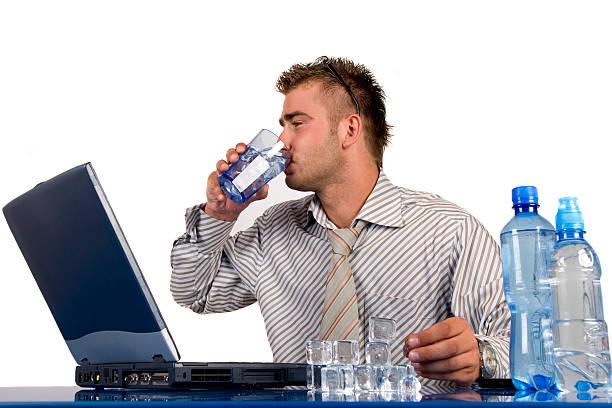 buisnessman am arbeitsplatz - leitungswasser trinken stock-fotos und bilder