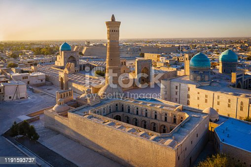 Sunset over the famous Kalyan Poi Kalon Minaret, Poi Kalan or Po-i-Kalyan and Mir Arab Madrasah in the center of the old town of Bukhara - Buxoro - Бухорo. Aerial Drone Point view at Sunset. Itchan Kala, Bukhara, Khorezm Region, Uzbekistan, Central Asia.