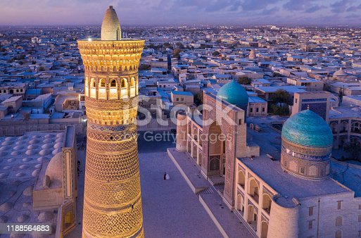 Aerial view of illuminated Kalyan Minaret at Po-i-Kalyan - Poi Kalan during colorful sunset twilight over the famous old town in the city of Bukhara - Buxoro - Бухорo. Iconic Kalyan Minaret in the foreground, Miri Arab Madressa on the right. Unrecognizable wedding couple - bride and groom in the middle of the Poi Kalan Compex. Drone Point of View. Itchan Kala, Bukhara - Бухорo, Khorezm Region, Uzbekistan, Central Asia.