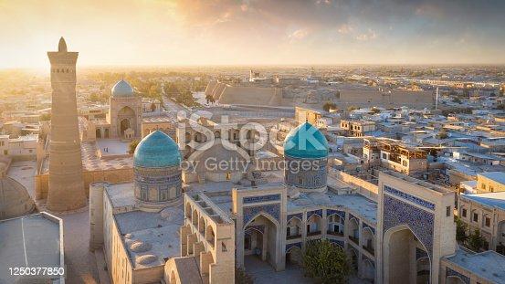 Sunset Panorama over the famous Kalyan Poi Kalon, Poi Kalan or Po-i-Kalyan and Kalon Mosque with courtyard in the old town of Bukhara - Buxoro - Бухорo. Aerial Drone Point View at Sunset. Itchan Kala, Bukhara, Khorezm Region, Uzbekistan, Central Asia.