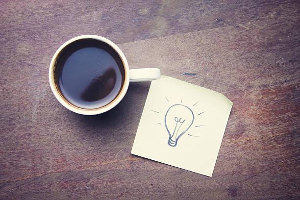 glühbirne auf papier und kaffee - filzunterlage stock-fotos und bilder