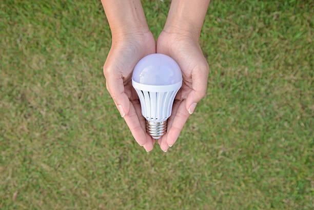 led-leuchtmittel-technologie in unserer hand sparen - glühbirne e27 stock-fotos und bilder