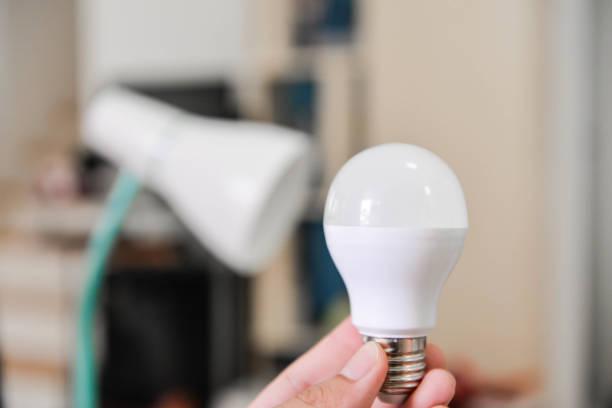 led-lampe - ausgewählt die birne mit elektrische lampe, lampenwechsel, led-lampe, lampe für das energiesparen zu verwenden - glühbirne auswechseln stock-fotos und bilder