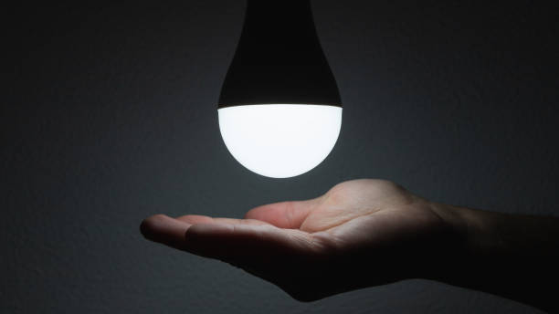 LED bulb with lighting in the human hand with dark background stock photo
