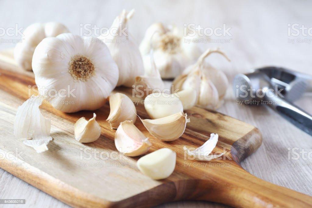 Bulbos de ajo en ajo y tablero de corte de prensa - foto de stock
