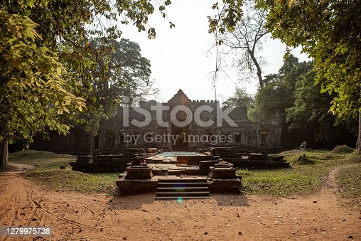 The sun shines over an ancient building in Angkor Wat