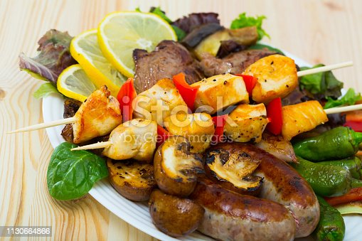 Bulgarian cuisine. Meshana skara - mixed grill plate from meat, sausages, vegetables and greens