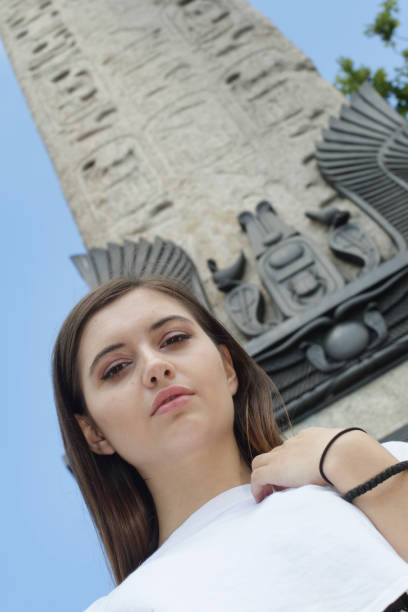 bulgarian outdoor girl beauty below head of egyptian sphinx - whiteway bulgarian outdoor girl stock photos and pictures