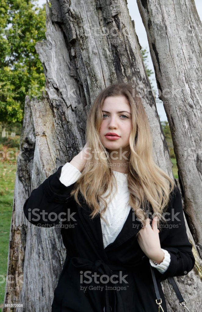 Bulgarian outdoor girl leaning on trunk of dead tree stock photo