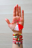 Bulgarian traditional spring decor martenitsa bracelets, holding in hand, wooden background. Baba Marta holiday, backdrop.