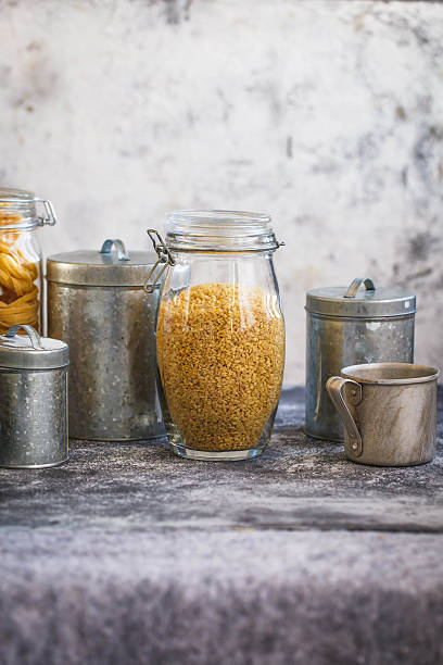 Bulgur Cereal In Glass Jar Over the Kitchen Table stock photo