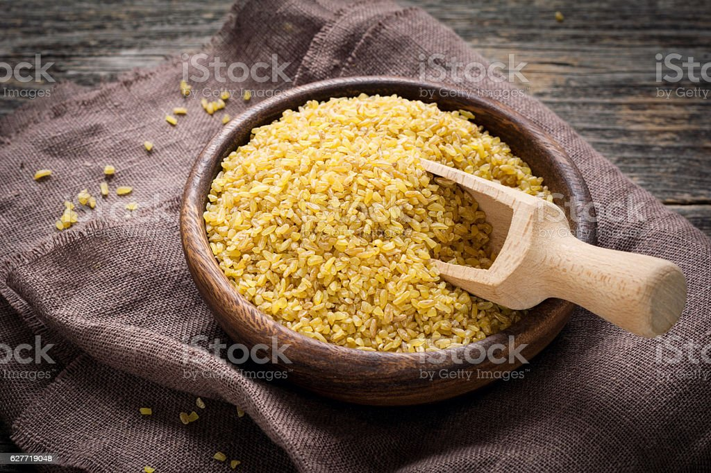 Bulgur, raw wheat grains in wooden bowl - Photo