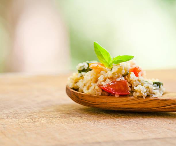 bulgur-salat auf einem löffel der olive wood - couscous salat minze stock-fotos und bilder