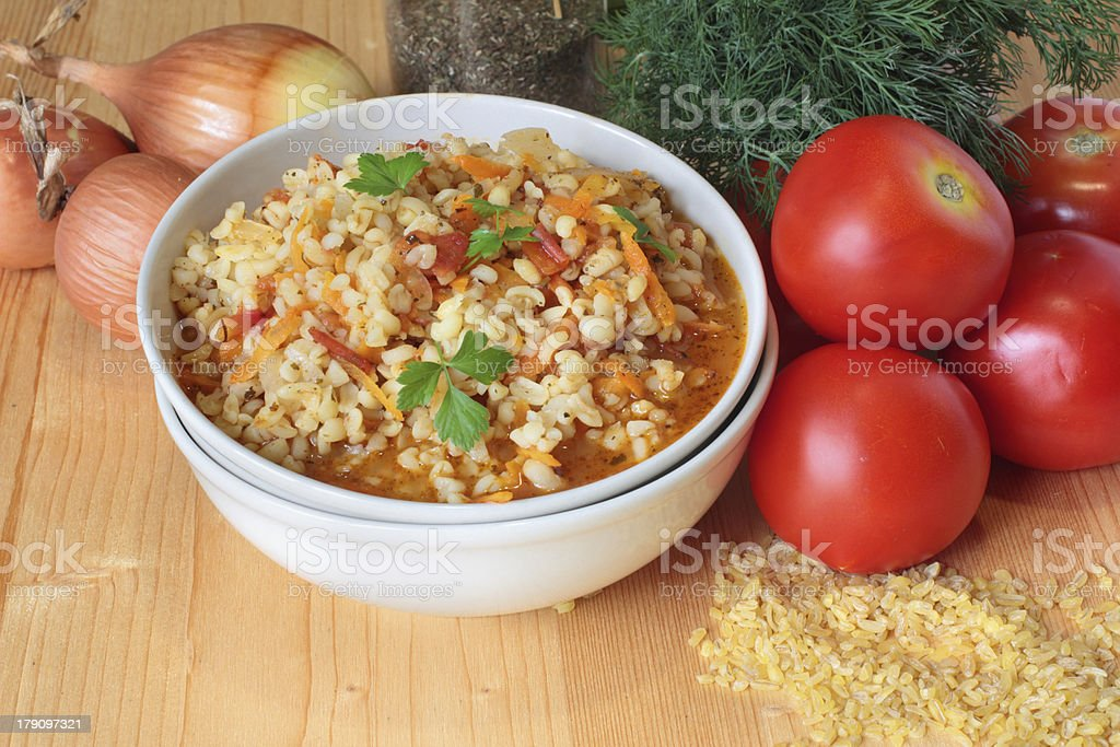 Bulgur with tomatoes, carrots and mint on the wooden table royalty-free stock photo