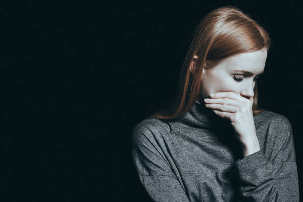Bulimic woman covering her mouth stock photo