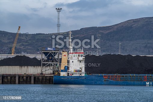 Belfast, Northern Ireland, United Kingdom - March 15, 2020: A bulk cargo ship unloading cargo of coal at a commercial dock of the Port of Belfast.