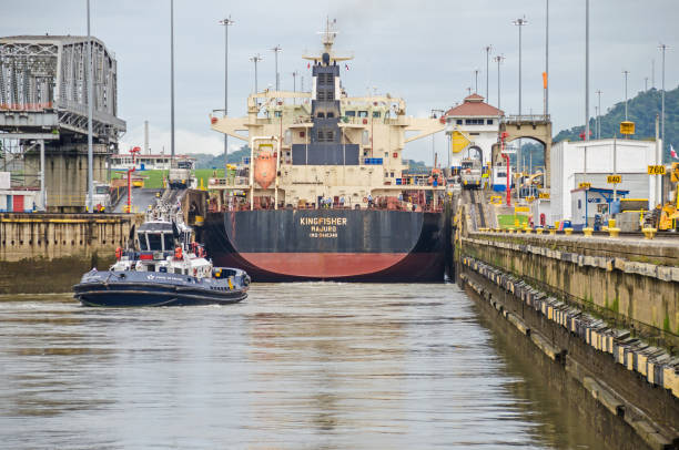 Bulk Carrier KINGFISHER entering the Miraflores Locks Panama City, Panama - 4 November, 2017: Bulk Carrier KINGFISHER currently sailing under the flag of Marshall Islands entering the Miraflores Locks to transit the Panama Canal and one tugboat  and two electric locomotives or mules ready to manoeuvre it. deadweight stock pictures, royalty-free photos & images