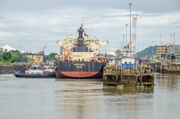 Bulk Carrier KINGFISHER entering the Miraflores Locks Panama City, Panama - 4 November, 2017: Bulk Carrier KINGFISHER currently sailing under the flag of Marshall Islands entering the Miraflores Locks to transit the Panama Canal and two tugboats ready to manoeuvre it. deadweight stock pictures, royalty-free photos & images