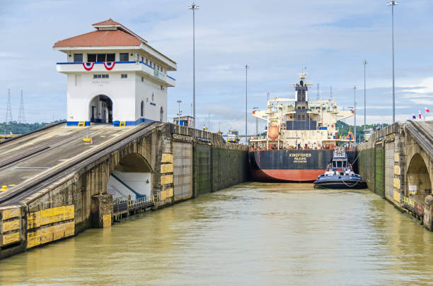 Bulk Carrier KINGFISHER entering the Pedro Miguel Locks Panama City, Panama - 4 November, 2017: Bulk Carrier KINGFISHER currently sailing under the flag of Marshall Islands entering the Pedro Miguel Locks to transit the Panama Canal with the help of a tugboat and electric locomotives or mules on each side. deadweight stock pictures, royalty-free photos & images