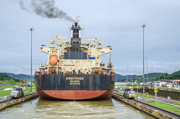Bulk Carrier KINGFISHER exiting the Miraflores Locks Panama City, Panama - 4 November, 2017: Bulk Carrier KINGFISHER just passed through the Miraflores Locks and lifted with the help of two electric locomotives or mules, one on each side, ready to exit the locks into the Miraflores Lake of Panama Canal. deadweight stock pictures, royalty-free photos & images