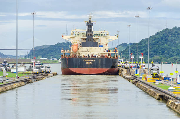 Bulk Carrier KINGFISHER exiting the Miraflores Locks Panama City, Panama - 4 November, 2017: Bulk Carrier KINGFISHER just passed through the Miraflores Locks with the help of  electric locomotives or mules, exiting the locks into the Miraflores Lake of Panama Canal. deadweight stock pictures, royalty-free photos & images
