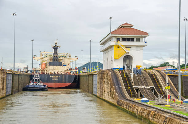 Bulk Carrier KINGFISHER passing through the Miraflores Locks Panama City, Panama - 4 November, 2017: Bulk Carrier KINGFISHER currently sailing under the flag of Marshall Islands in the Miraflores Locks, one electric locomotive or mule on each side and a tugboat ready to manoeuvre it through the chamber of Panama Canal. deadweight stock pictures, royalty-free photos & images