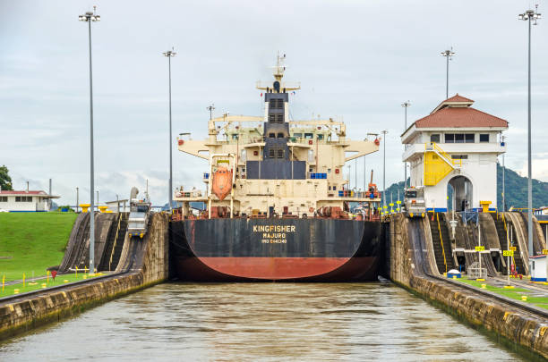 Bulk Carrier KINGFISHER passing through the Miraflores Locks Panama City, Panama - 4 November, 2017: Bulk Carrier KINGFISHER currently sailing under the flag of Marshall Islands in the Miraflores Locks, one electric locomotive or mule on each side ready to manoeuvre it through the chamber of Panama Canal. deadweight stock pictures, royalty-free photos & images
