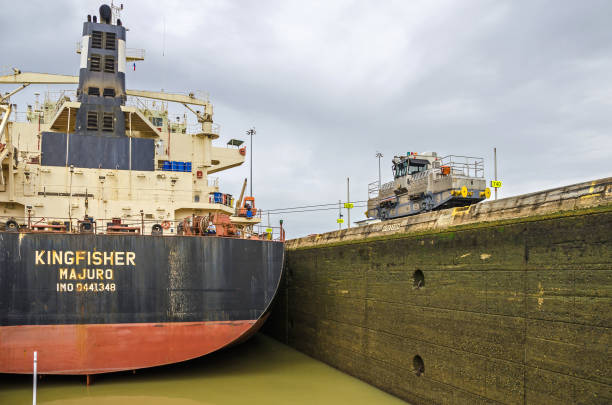 Bulk Carrier KINGFISHER passing through the Miraflores Locks Panama City, Panama - 4 November, 2017: Bulk Carrier KINGFISHER currently sailing under the flag of Marshall Islands in the Miraflores Locks, ready to lift with the help of the electric locomotive or mule manoeuvering it through the chamber of Panama Canal. deadweight stock pictures, royalty-free photos & images