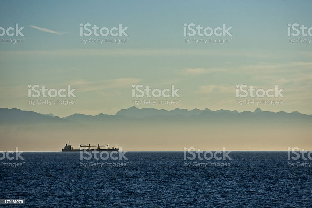Bulk freighter cruises Inside Passage silhouetted against mountain range stock photo
