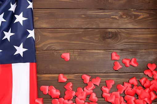 istock Bulk red hearts and USA flag, on a wooden table. 613781268