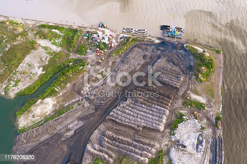 istock Bulk territories on the shore of the sea bay, dumping of soil artificial island aerial top view. 1176208320