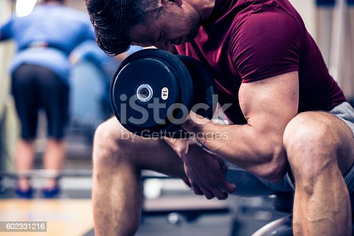 Muscular young man doing exercises for biceps muscles with dumbbells on in a gym.