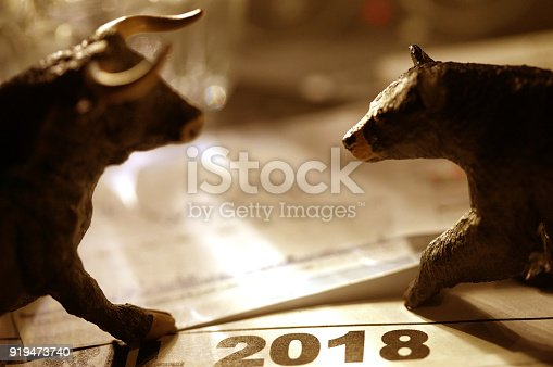 shot of bull and bear figurine with stock charts