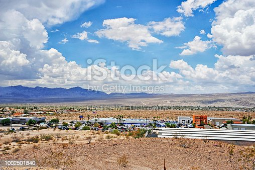 Bull Head City, Arizona, USA - July 12, 2018: This view of Bull Head City in Arizona is from a high road in town, this view is overlooking many shops and retail outlets, streets, signs and advertisements, farter from the main street there are residental homes and then the desert and in the distance mountains and this under beautiful July clouds making this a great view.